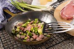 Προετοιμασία ενός πολύ ιρλανδικού πιάτου colcannon με το κρεμμύδι και το baco άνοιξη στοκ φωτογραφίες