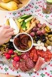 Προετοιμασία μιας πιατέλας κομμάτων με τα κρέατα και το τυρί Στοκ Φωτογραφίες