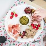 Προετοιμασία μιας πιατέλας κομμάτων με τα κρέατα και το τυρί Στοκ Εικόνες