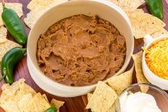 Προετοιμασία της εμβύθισης φασολιών με τα jalapenos, την ξινά κρέμα και το τυρί Cheddar γ Στοκ Εικόνες