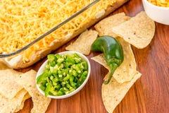 Προετοιμασία της εμβύθισης φασολιών με τα jalapenos, την ξινά κρέμα και το τυρί Cheddar γ Στοκ Φωτογραφία