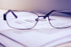Προετοιμασία της επιχειρησιακής έκθεσης Ένας σωρός των εγγράφων, ενός σημειωματάριου και των γυαλιών στον πίνακα Στοκ εικόνες με δικαίωμα ελεύθερης χρήσης
