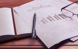 Προετοιμασία της επιχειρησιακής έκθεσης Ένας σωρός των εγγράφων, ενός σημειωματάριου και των γυαλιών στον πίνακα Στοκ Φωτογραφία