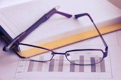 Προετοιμασία της επιχειρησιακής έκθεσης Ένας σωρός των εγγράφων, ενός σημειωματάριου και των γυαλιών στον πίνακα Στοκ εικόνα με δικαίωμα ελεύθερης χρήσης