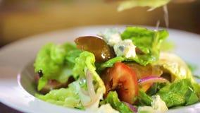 Προετοιμασία της φρέσκιας σαλάτας με τα πράσινες φύλλα, το κρεμμύδι και τις ντομάτες απόθεμα βίντεο