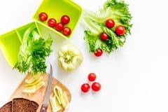 Προετοιμασία του ελαφριού φυτικού μεσημεριανού γεύματος με τις ντομάτες κερασιών, σαλάτα, ψωμί, paprica στην άσπρη τοπ άποψη υποβ Στοκ Εικόνες