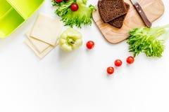 Προετοιμασία του ελαφριού φυτικού μεσημεριανού γεύματος με τις ντομάτες, σαλάτα, ψωμί, paprica, τυρί στην άσπρη τοπ άποψη υποβάθρ Στοκ φωτογραφία με δικαίωμα ελεύθερης χρήσης