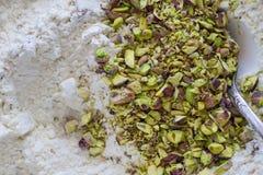 Προετοιμασία του κέικ φυστικιών από τα καρύδια με ένα ασημένιο κουτάλι Στοκ Εικόνες