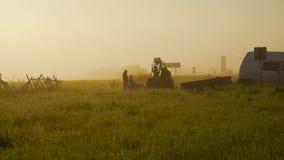 Προετοιμασία του καλαθιού μπαλονιών για την πτήση, ξημερώματα στον τομέα η δροσιά στη χλόη και οι μαλακές ακτίνες απόθεμα βίντεο