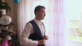 Προετοιμασία του νεόνυμφου για τη γαμήλια τελετή Ο νεόνυμφος βάζει σε μια εορταστική φανέλλα σε ένα δωμάτιο με τις σφαίρες απόθεμα βίντεο