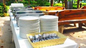 Προετοιμασία του πίνακα μπουφέδων με τους δίσκους, τα πιάτα, τα κουτάλια και τα δίκρανα τροφίμων για το κόμμα μεσημεριανού γεύματ στοκ εικόνες