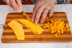 Προετοιμασία τροφίμων - τεμαχισμός της κολοκύθας με το μαχαίρι στοκ φωτογραφία με δικαίωμα ελεύθερης χρήσης