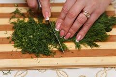 Προετοιμασία τροφίμων - τεμαχισμός του άνηθου με το μαχαίρι στοκ εικόνα