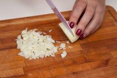 Προετοιμασία τροφίμων - τεμαχισμός των κρεμμυδιών με το μαχαίρι στοκ φωτογραφίες με δικαίωμα ελεύθερης χρήσης