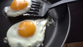 Προετοιμασία των ανακατωμένων αυγών στο καυτό τηγανίζοντας τηγάνι απόθεμα βίντεο