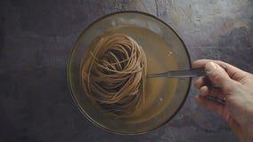 Προετοιμασία των νουντλς φαγόπυρου στο σπίτι, που ανακατώνει με ένα κουτάλι φιλμ μικρού μήκους