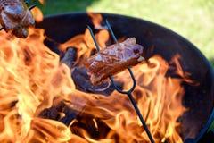 Προετοιμασία των λουκάνικων στην πυρκαγιά στρατόπεδων Στοκ Εικόνες