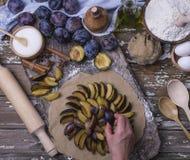 Προετοιμασία των σπιτικών φρέσκων φυσικών εύγευστων πιτών από τα δαμάσκηνα με τη βοήθεια ενός θηλυκού χεριού σε ένα ξύλινο υπόβαθ στοκ εικόνες