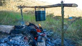 Προετοιμασία των τροφίμων στην πυρά προσκόπων στην άγρια στρατοπέδευση Στοκ Φωτογραφίες