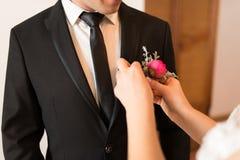 Προετοιμασίες για το γάμο ο νεόνυμφος Η νύφη βάζει στη μπουτονιέρα στο σακάκι νεόνυμφων ` s Ρομαντική γαμήλια στιγμή Στοκ εικόνα με δικαίωμα ελεύθερης χρήσης