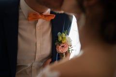 Προετοιμασίες για το γάμο ο νεόνυμφος Η νύφη βάζει στη μπουτονιέρα στο σακάκι νεόνυμφων ` s Ρομαντική γαμήλια στιγμή Στοκ Εικόνες