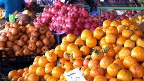 Προθήκη με Persimmon, τα μήλα, τα αχλάδια, τα ρόδια και τα διαφορετικά φρούτα στην αγορά οδών απόθεμα βίντεο