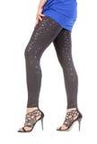 Προκλητικά μοντέρνα πόδια στα λαμπυρίζοντας μαύρα leggins Στοκ Εικόνες