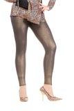 Προκλητικά μοντέρνα πόδια στα λαμπυρίζοντας χρυσά leggins Στοκ Εικόνες