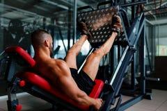 Προκλητικά μυϊκά άτομα χρησιμοποιώντας μια μηχανή Τύπου ποδιών και τοποθετώντας τα πόδια του στην πλατφόρμα σε ένα σκοτεινό ζωηρό Στοκ Φωτογραφία
