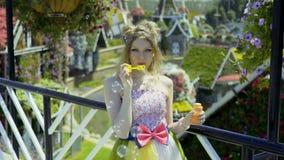 Προκλητικές νέες ξανθές φυσαλίδες σαπουνιών γυναικών φυσώντας στον κήπο λουλουδιών Το αρκετά ονειρεμένος χαριτωμένο κορίτσι στο α φιλμ μικρού μήκους