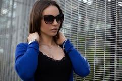 Προκλητική αρκετά νέα γυναίκα hipster στα μοντέρνα γυαλιά ηλίου σε μια μαύρη εκλεκτής ποιότητας μπλούζα σε ένα μπλε πλεκτό ακρωτή στοκ φωτογραφία