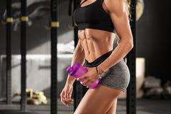 Προκλητική γυναίκα ικανότητας που παρουσιάζει τα ABS και επίπεδη κοιλιά στη γυμναστική Όμορφο μυϊκό κορίτσι, διαμορφωμένη κοιλιακ στοκ εικόνες