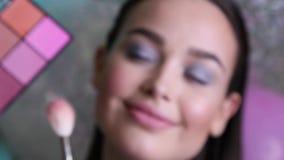 προκλητική γυναίκα με τη σκοτεινή τρίχα με το βράδυ makeup στα κομψά ενδύματα που θέτουν στο στούντιο, makeup καλλιτέχνης που κάν απόθεμα βίντεο