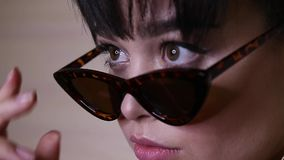 Προκλητική γυναίκα με τη σκοτεινή τρίχα με το βράδυ makeup στα κομψά ενδύματα και τα γυαλιά ηλίου που φλερτάρουν στη κάμερα απόθεμα βίντεο