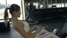 Προκλητική γυναίκα που τραβά το βάρος στον αθλητικό εκπαιδευτή στο εσωτερικό λεσχών ικανότητας φιλμ μικρού μήκους