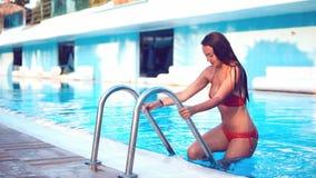 Προκλητική γυναίκα στο μπικίνι που προέρχεται από την πισίνα απόθεμα βίντεο
