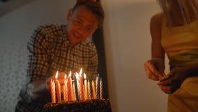 Προκλητική κυρία και όμορφα κεριά φω'των τύπων στο νόστιμο κέικ γενεθλίων Prepearing για το κόμμα απόθεμα βίντεο