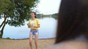 Προκλητική νέα παίζοντας πετοσφαίριση γυναικών με τους φίλους της σε μια αμμώδη παραλία κοντά σε μια λίμνη Όμορφο κορίτσι στα σύν απόθεμα βίντεο