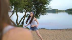 Προκλητική νέα παίζοντας πετοσφαίριση γυναικών με τους φίλους της σε μια αμμώδη παραλία κοντά σε μια λίμνη Όμορφο κορίτσι στα σύν φιλμ μικρού μήκους