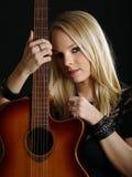 Προκλητική ξανθή γυναίκα με την ακουστική κιθάρα Στοκ Εικόνα