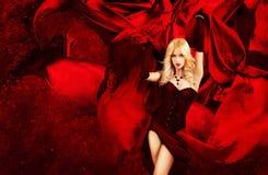 Προκλητική ξανθή γυναίκα φαντασίας με το ράντισμα του κόκκινου μεταξιού Στοκ Εικόνα