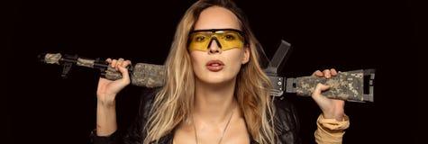 Προκλητική ξανθή επικίνδυνη γυναίκα με το αυτόματο τουφέκι στοκ εικόνες
