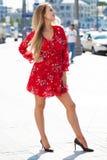 Προκλητική ξανθή πρότυπη τοποθέτηση στην οδό θορίου στο κόκκινο θερινό φόρεμα στοκ εικόνα