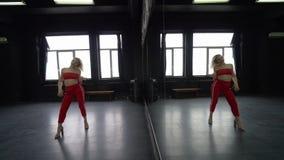 Προκλητικοί ξανθοί χοροί κοριτσιών στο στούντιο κοντά στον καθρέφτη απόθεμα βίντεο