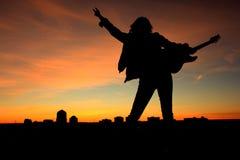 Προκλητικός βράχος γυναικών - και - ηλιοβασίλεμα ρόλων Στοκ εικόνες με δικαίωμα ελεύθερης χρήσης