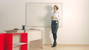 προκλητικός δάσκαλος με έναν γράφοντας πίνακα στην τάξη ή το γραφείο απόθεμα βίντεο