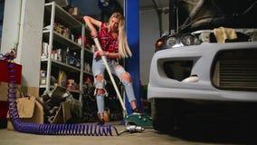 Προκλητικός ξανθός σε ένα γκαράζ επισκευάζει ένα αυτοκίνητο απόθεμα βίντεο
