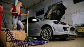Προκλητικός ξανθός σε ένα γκαράζ επισκευάζει ένα αυτοκίνητο φιλμ μικρού μήκους
