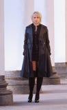 Προκλητικός ξανθός στο μίνι φόρεμα τζιν και τις μαύρες γυναικείες κάλτσες στοκ φωτογραφία με δικαίωμα ελεύθερης χρήσης