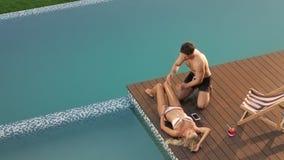 Προκλητικό άτομο που εφαρμόζει το suntan λοσιόν στο θηλυκό σώμα Ευτυχές ζεύγος που απολαμβάνει την ηλιοθεραπεία απόθεμα βίντεο